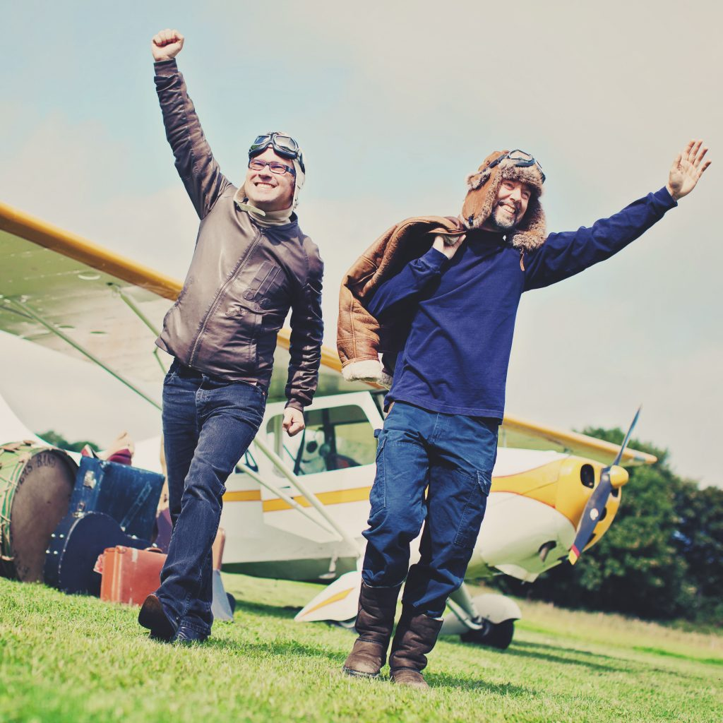 Leo and Anto emerge from a plane, wearing Biggles helmets