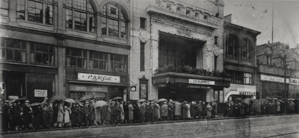 A black and white image of a long queue outside the Regal cinema in Sauchiehall Street.