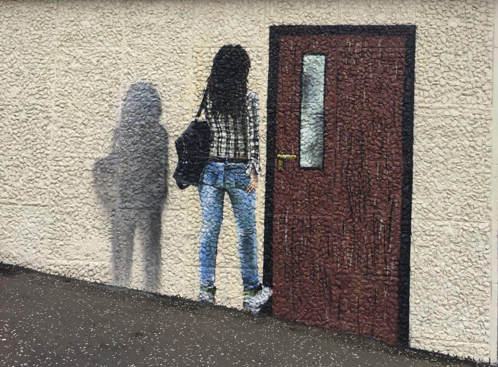 Mural of girl walking through wall