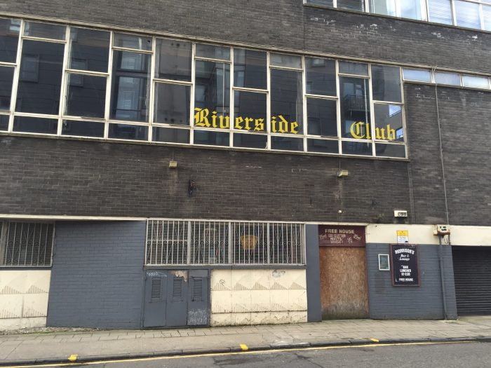 The old Riverside Club sign in the window of what used to be Graphical House