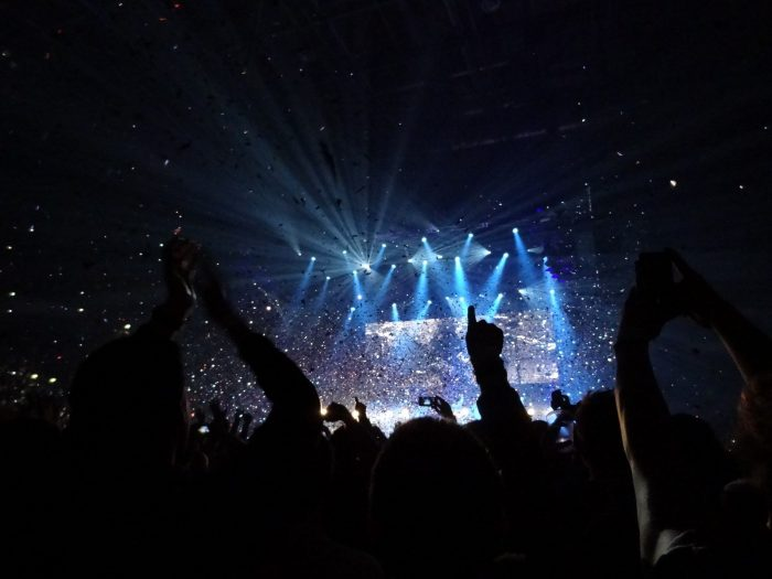 Manchester Arena, floodlit stage seen through upraised arms Photo Andy Nugent: CC By-NC-ND 2.0