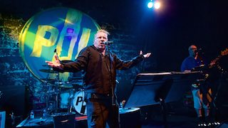 Johnny Rotten (now John Lyden) standing on the Ironworks stage with outstretched arms, in 2016. Photo courtesy Paul Campbell